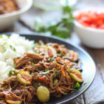 Tender strands of pull apart flank steak nestled in a spicy tomato sauce makes this slow cooker spicy shredded beef something you should not miss.