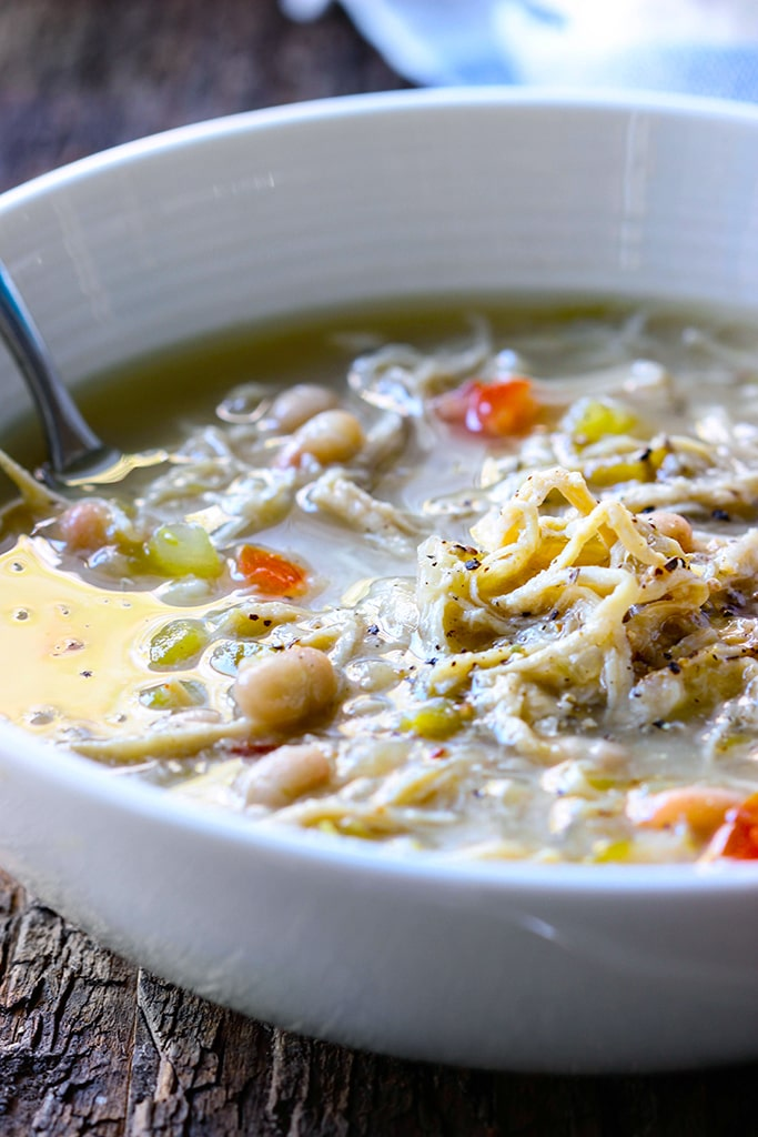 A slow cooker white chicken chili with tender chicken and beans simmered in a thick broth with green chilies, onions and celery. Pair it with your favorite toppings.